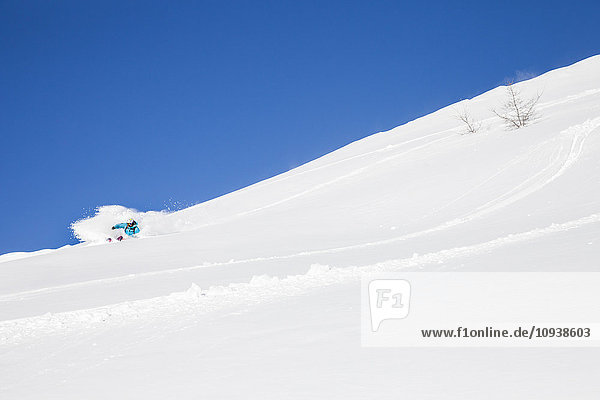 Woman skiing downhill in powder snow