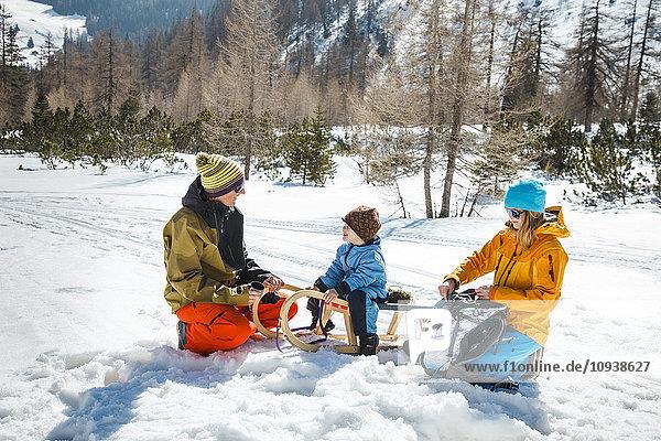 Family with sledge taking a break in snowy landscape