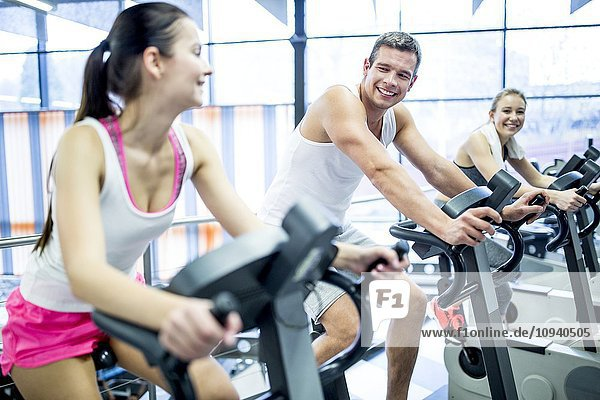 Young men and women working out in gym
