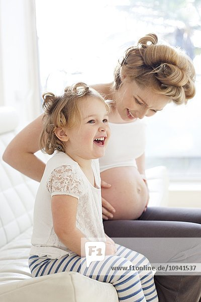 Pregnant woman and daughter smiling