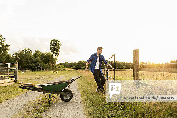 Mann öffnet Tor mit Schubkarre auf unbefestigtem Weg gegen den Himmel auf dem Bauernhof