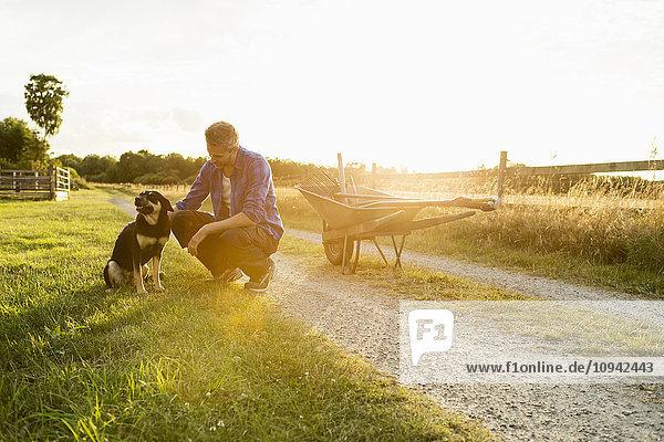Mann mit Hund im Grasfeld am Bauernhof gegen den Himmel