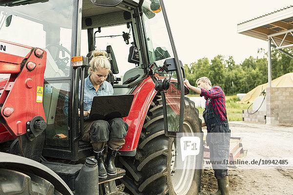 Frau benutzt Laptop  während der Mann am Traktor steht.