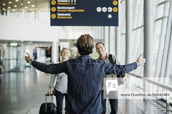 Rückansicht des Geschäftsmannes mit ausgestreckten Armen bei der Begrüßung der Kollegen am Flughafen