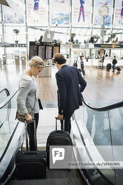 Rückansicht von Geschäftsleuten mit Gepäck auf der Rolltreppe des Flughafens
