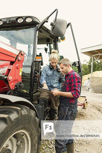 Frau bespricht mit männlichem Arbeiter über Dokument mit dem Traktor auf dem Bauernhof