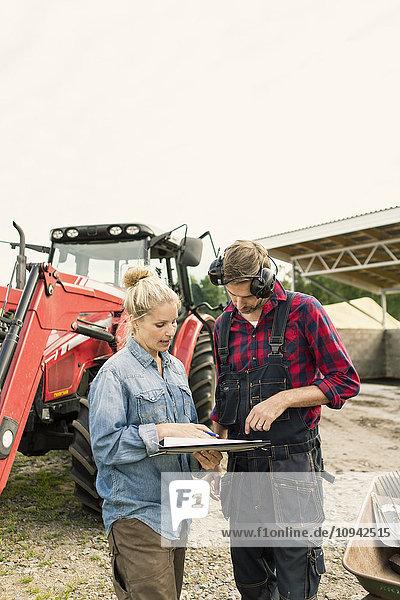 Seriöse Frau diskutiert mit Mann über Dokument mit Traktor auf dem Bauernhof