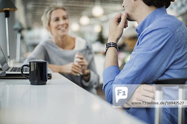 Mittelteil eines Geschäftsmannes  der mit einer Kollegin im Flughafencafé sitzt.