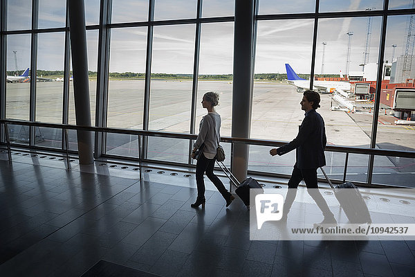 Geschäftsleute mit Gepäck am Flughafen Geschäftsleute mit Gepäck am Flughafen