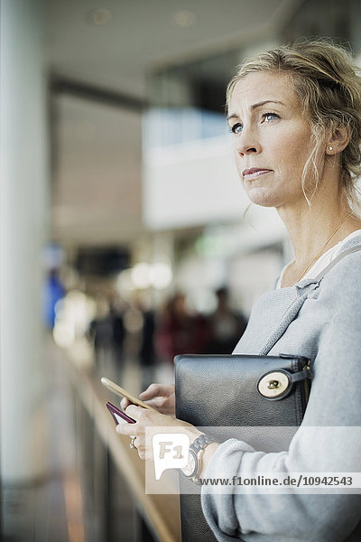 Businesswoman looking away while holding smart phone at airport