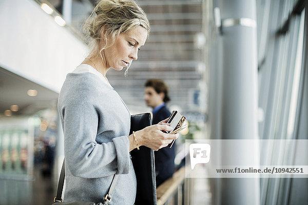 Seitenansicht der Geschäftsfrau mit Smartphone am Flughafen