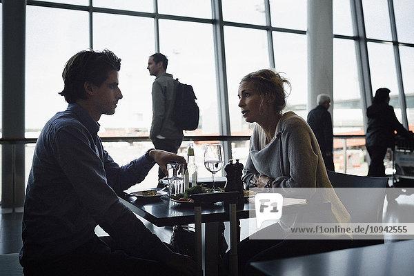 Geschäftsleute beim Essen im Cafe am Flughafen