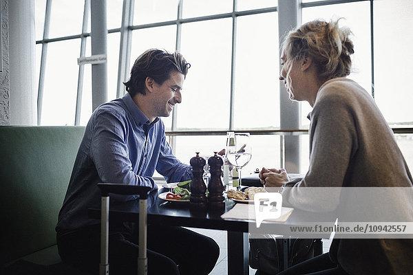 Seitenansicht der Geschäftsleute beim Essen im Cafe am Flughafen