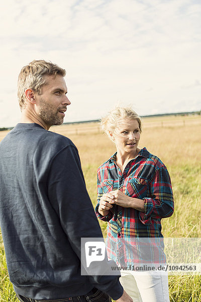 Man and woman looking away while standing on grassy field against sky