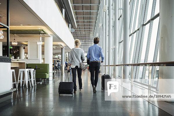 Rückansicht von Geschäftsleuten mit Gepäck am Flughafen