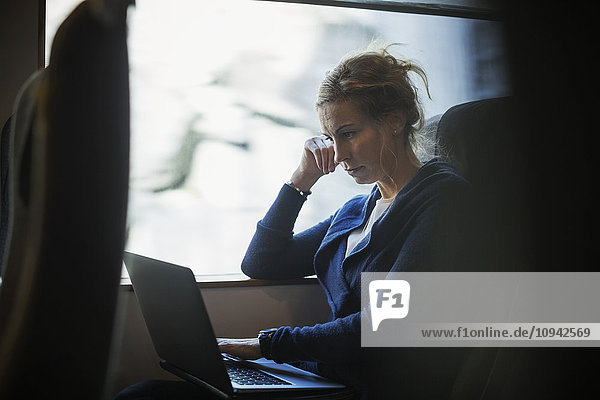 Geschäftsfrau mit Laptop im Zug