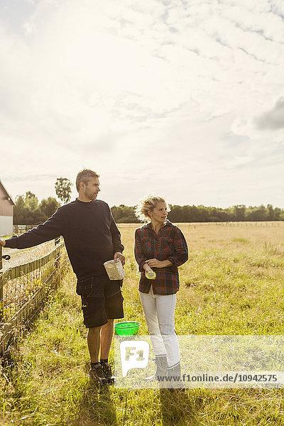 Mann und Frau reden  während sie auf einer Wiese gegen den Himmel stehen.