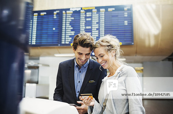 Glückliche Geschäftsleute  die am Flughafen auf Kreditkarte schauen
