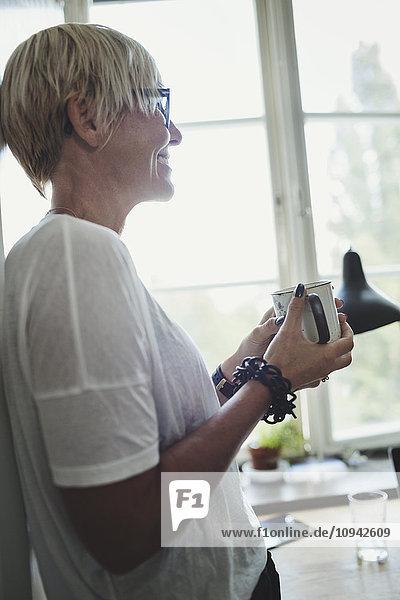 Seitenansicht des lächelnden Industriedesigners mit Kaffeetasse in der Küche