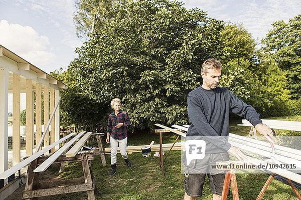 Mann mit Bauernfrau beim Schuppenbau gegen Bäume