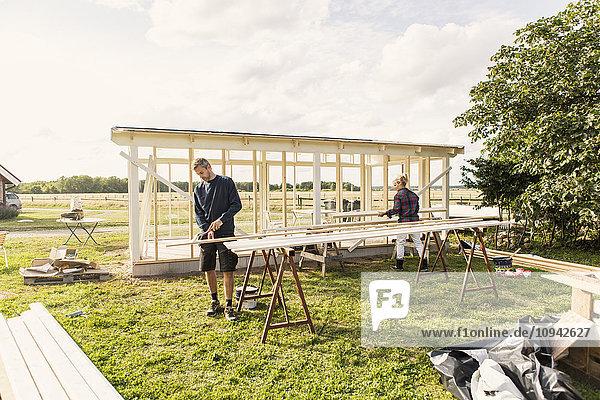 Mann und Frau beim Schuppenbau auf dem Bauernhof gegen den Himmel