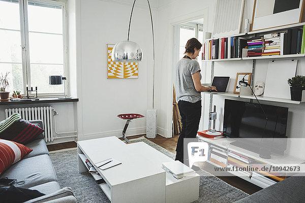 Rückansicht des Industriedesigners mit Laptop im Regal zu Hause