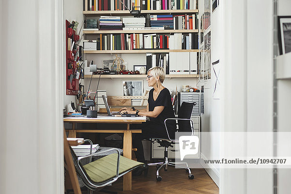 Female product designer using laptop at home office