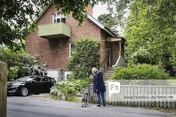 Seniorin und Hund vor dem Haus stehend