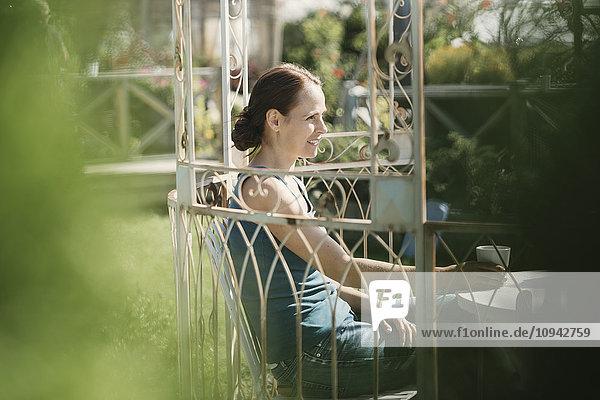 Fröhliche erwachsene Frau mit Kaffeetasse im Hinterhof