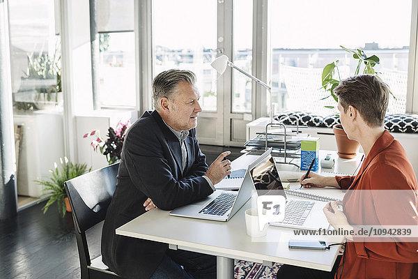 Geschäftsmann im Gespräch mit Kollegen am Schreibtisch