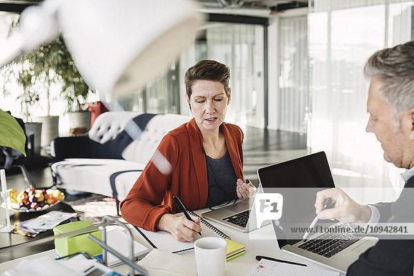 Geschäftsfrau beim Schreiben im Gespräch mit Kollegen