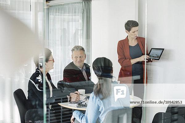 Geschäftsfrau zeigt digitales Tablett an Kollegen im Büro