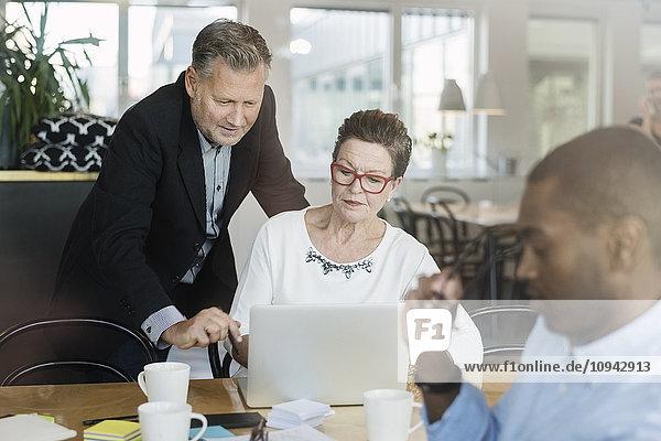 Geschäftsmann und Frau suchen im Laptop  während sie am Tisch sitzen.