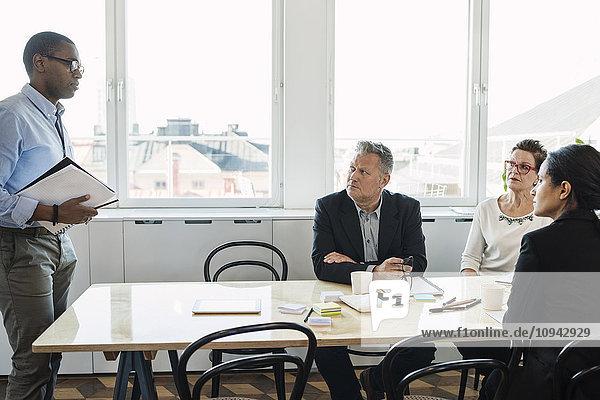 Geschäftsmann erklärt den Kollegen während der Besprechung im Büro