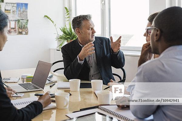 Reife Geschäftsleute erklären den Mitarbeitern im Büro
