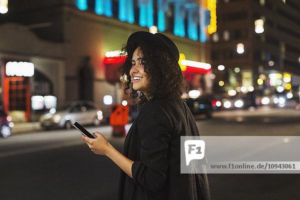 Glückliche Frau schaut weg  während sie nachts ein Smartphone in der Stadt hält.