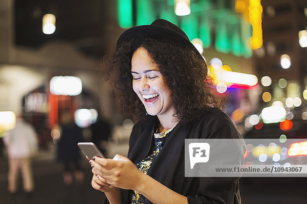 Young woman laughing while using smart phone in city at night