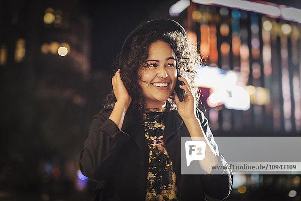 Fröhliche junge Frau schaut weg  während sie nachts in der Stadt auf das Smartphone geht.