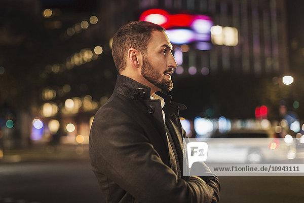Seitenansicht des Mannes  der nachts auf der Stadtstraße steht.