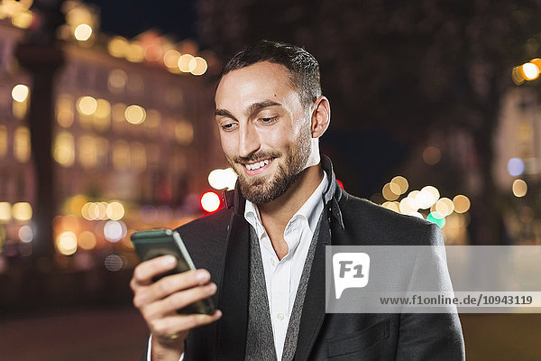 Happy man using smart phone in city at night