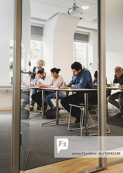 Lehrer unterrichtet Schüler in der Sprachklasse durch die offene Tür gesehen