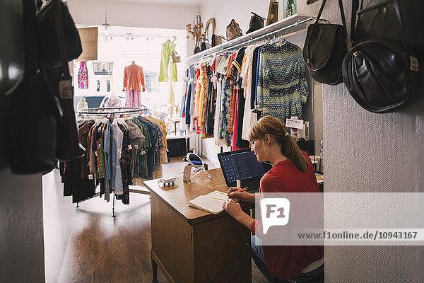 Frau arbeitet am Schreibtisch  während sie im Secondhand-Laden sitzt.