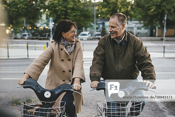 Glückliches Seniorenpaar mit Leihfahrrädern auf dem Parkplatz
