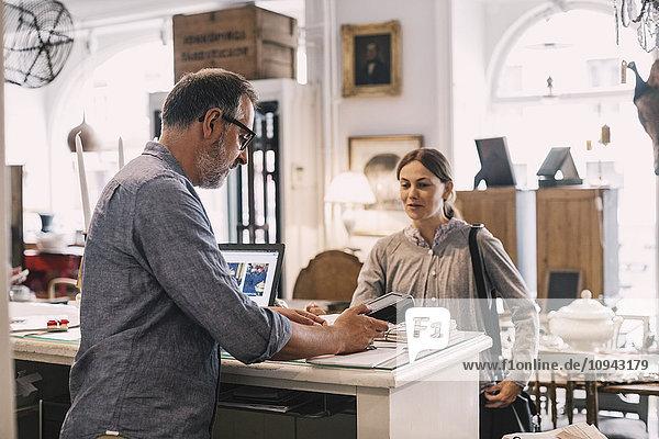 Besitzerin mit Kartenleser vor der Kundin am Ladentisch