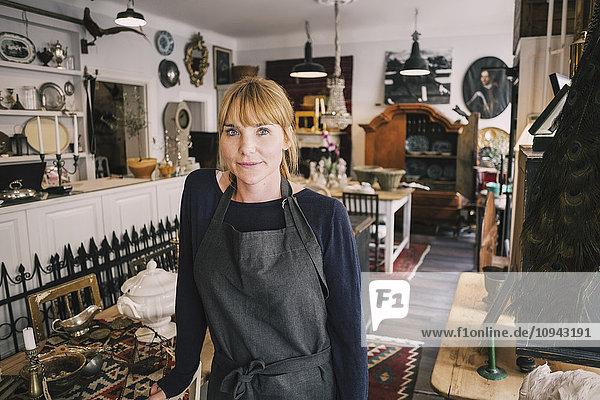 Porträt des selbstbewussten Besitzers am Tisch im Antiquitätengeschäft