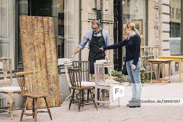 Die Kundin zeigt auf den Stuhl vor dem Antiquitätengeschäft.