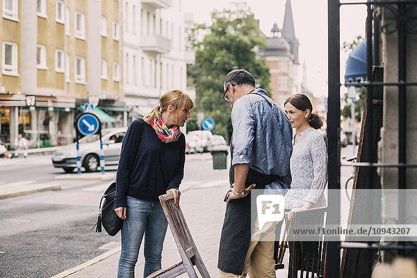Kundenstuhl im Gespräch mit den Besitzern außerhalb des Antiquitätengeschäfts