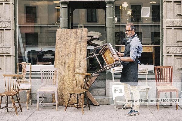 Volle Länge des Mannes  der den Stuhl hält  während er sich außerhalb des Ladens aufhält Volle Länge des Mannes, der den Stuhl hält, während er sich außerhalb des Ladens aufhält