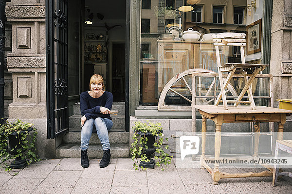 Die Besitzerin sitzt auf der Treppe eines Antiquitätengeschäftes.