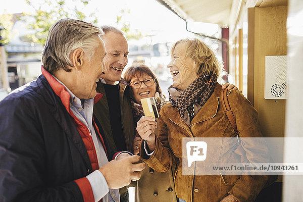 Glückliche Seniorin mit Freunden beim Kartenkauf per Kreditkarte im Musiktheater